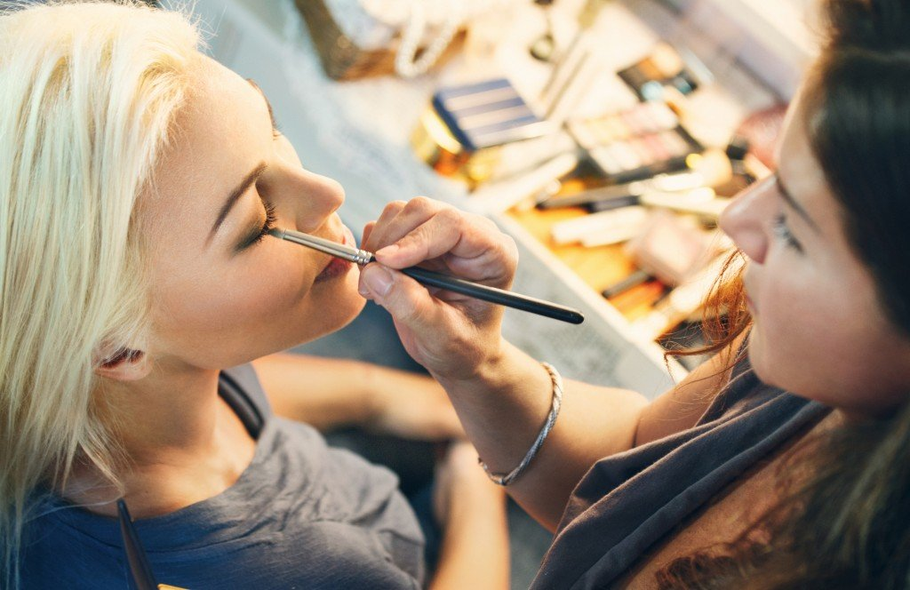 Closeup of adult blond woman having her makeup done by a professional at beauty salon. She;s sitting in front of large well lit mirror while beutician is applying eyeshadown on her eye lids. Top view.